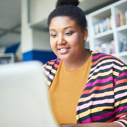 Woman in striped sweater on laptop